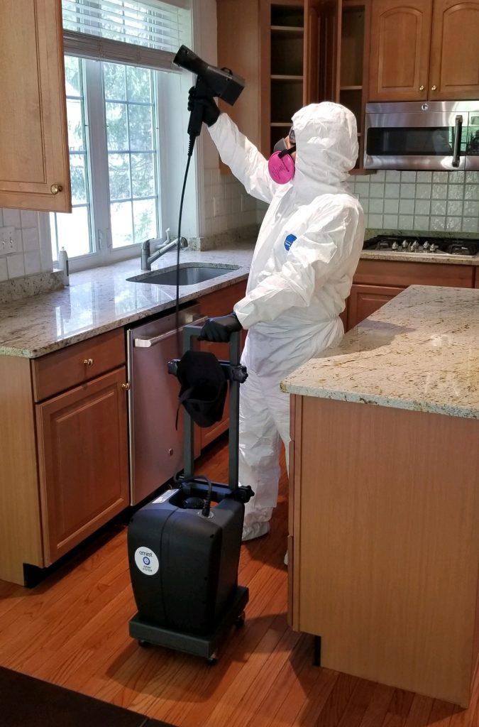 Man in a hazmat suit sanitizing window blinds - The Carpet Doctor Inc.