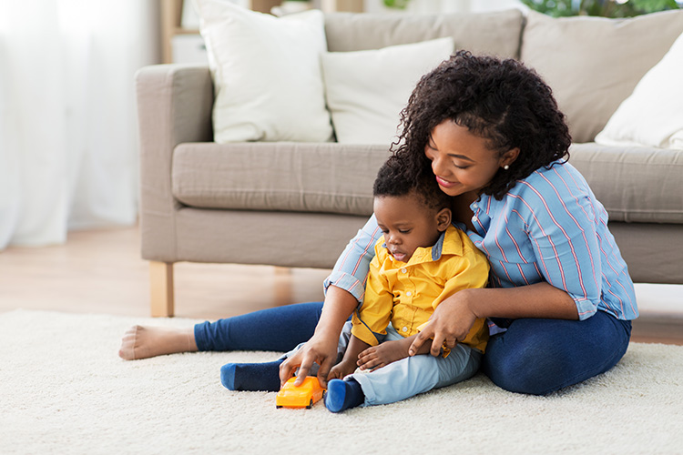 Mom and baby on a clean carpet playing with a toy car - The Carpet Doctor Inc.